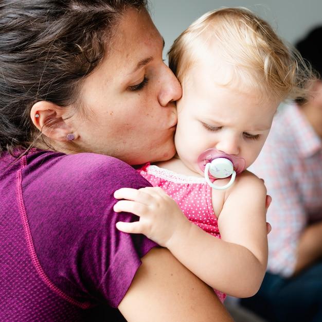 Mutter, die ihrem baby einen kuss gibt