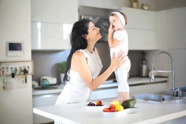 Mutter, die ihrem baby in der küche lebensmittel gibt
