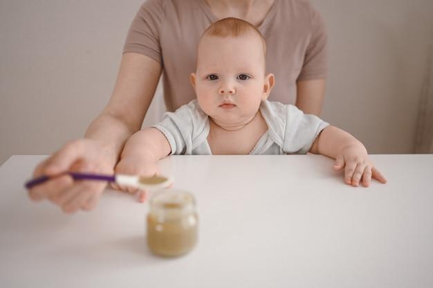 Mutter, die ihrem kleinen neugeborenen jungen gemüse- oder fruchtpüree aus glas mit löffel füttert