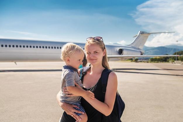 Mutter, die ihren babysohn durch das flugzeug hält. kaukasische familie am flughafen
