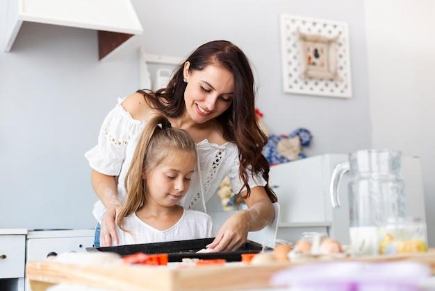 Mutter, die ihrer tochter beibringt, wie man kocht