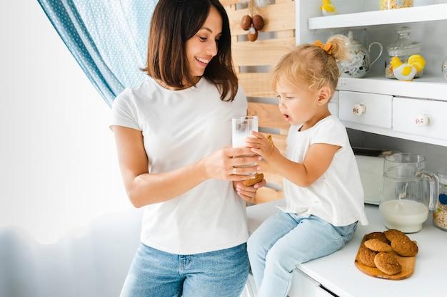 Mutter, die ihrer tochter ein glas milch anbietet