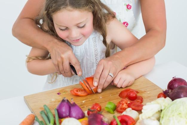 Mutter, die ihrer tochter hilft, tomate zu schneiden