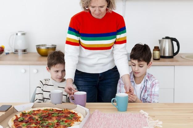 Mutter, die kinderhände desinfiziert, bevor sie pizza isst