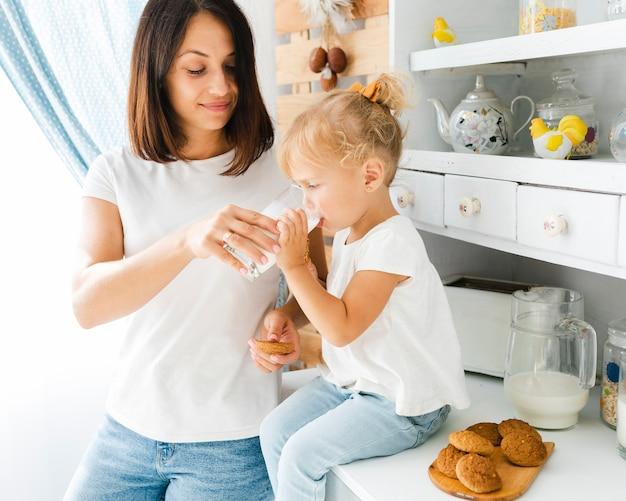 Mutter, die kleinem mädchen hilft, milch zu trinken