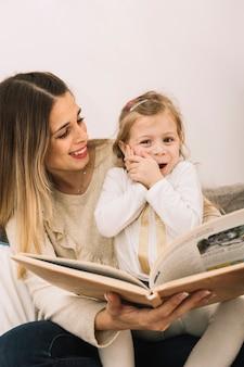 Mutter, die lustiges mädchen beim lesen betrachtet