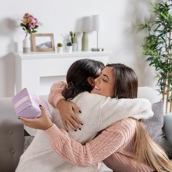 Mutter, die mädchen für geschenk umarmt
