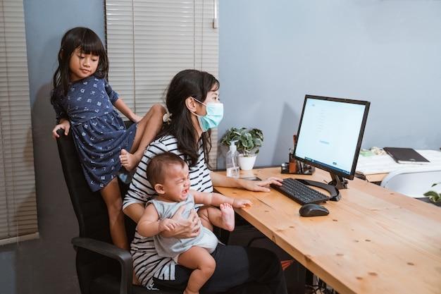 Mutter, die masken trägt, die ihr baby tragen, das nach hause arbeitet