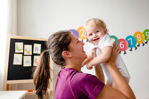 Mutter, die mit ihrem baby trägt und spielt