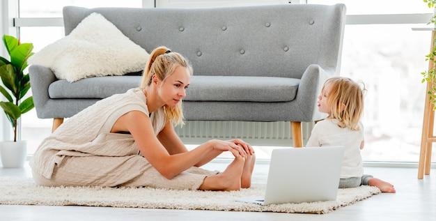 Mutter, die mit kind zu hause trainiert und online-video-training am laptop sieht