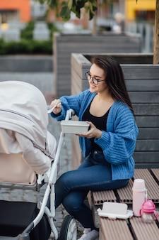 Mutter, die mit neugeborenem baby in kinderwagenfrau geht, die plastikbox hält und ihr baby füttert