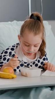 Mutter, die neben der kranken tochter sitzt, während sie das mittagessen isst und sich nach einer medizinischen operation erholt
