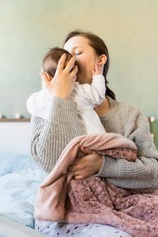 Mutter, die nettes baby in den armen küsst