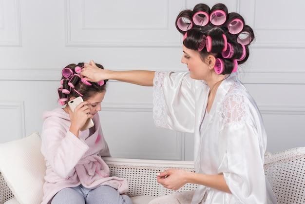 Mutter, die rosa lockenwickler in töchterhaare einsetzt