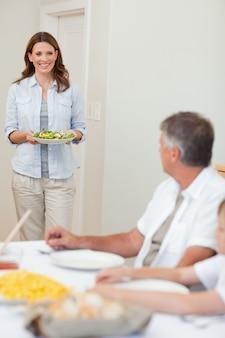 Mutter, die salat zum abendtisch holt