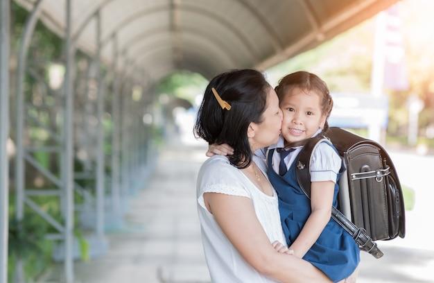 Mutter, die schulmädchen in der uniform vor dem gehen zur schule, liebes- und sorgfaltkonzept küsst
