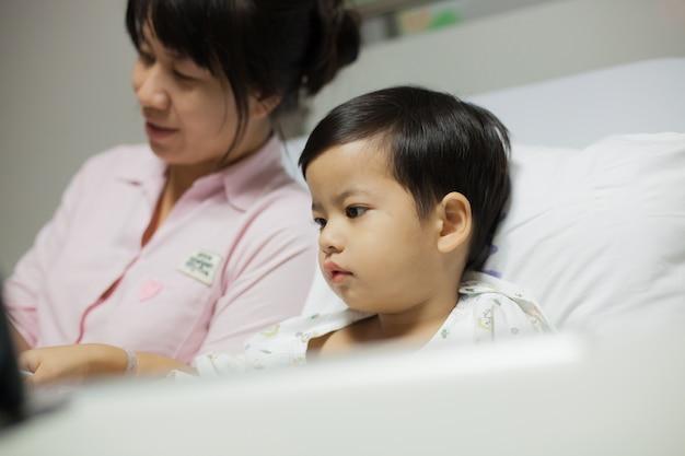Mutter, die seinem sohn auf einem krankenhausbett eine geschichte liest.