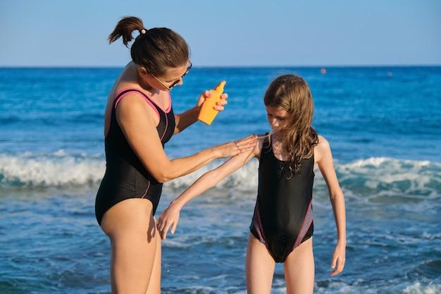 Mutter, die sonnenschutz auf tochter am strand anwendet