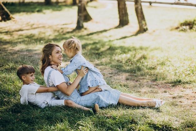 Mutter, die spaß mit sohn und tochter im park hat