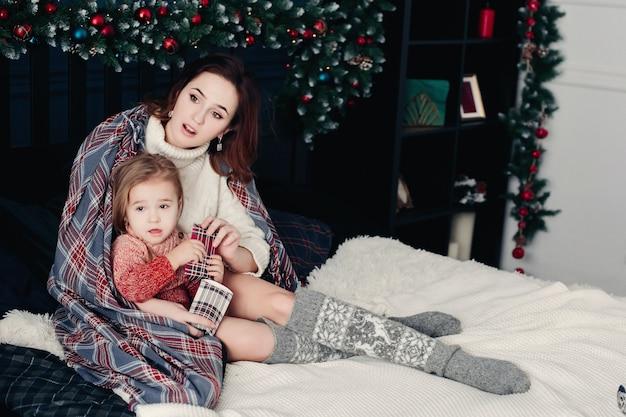 Mutter, die tochter am weihnachten umarmt