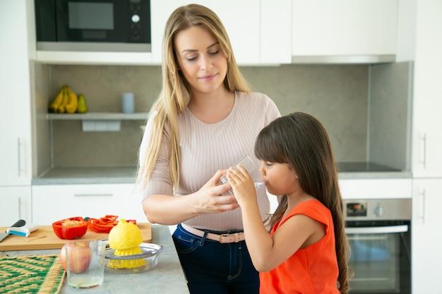 Mutter, die tochter glas wasser zu trinken gibt, während salat kocht und zitrone in der küche drückt. familienkochen oder gesundes lebensstilkonzept