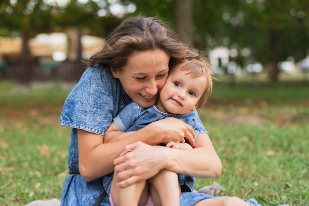 Mutter, die tochter im park umarmt