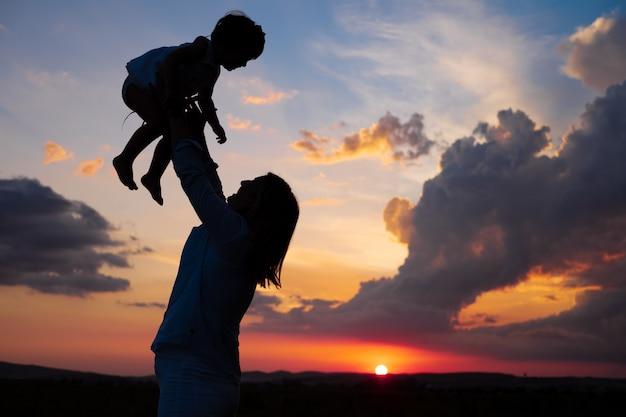 Mutter, die tochter in einem sonnenuntergang an der hintergrundbeleuchtung anhebt