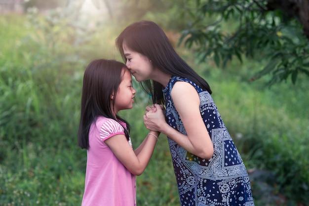 Mutter, die tochter küsst und hände mit liebe anhält