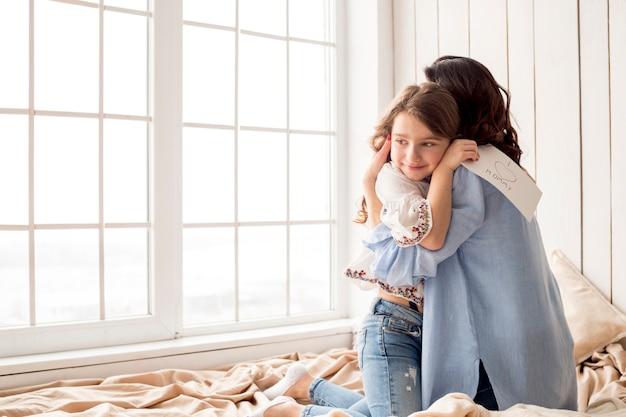 Mutter, die tochter mit grußkarte umarmt