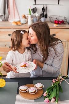 Mutter, die tochter mit kleinem kuchen küsst