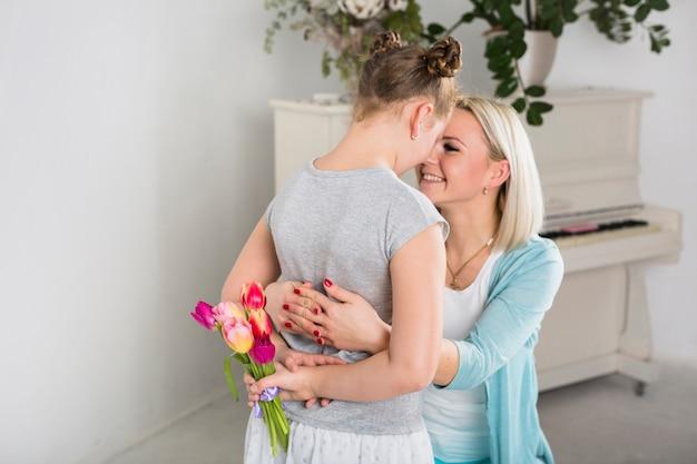 Mutter, die tochter mit verstecktem blumenstrauß umfasst