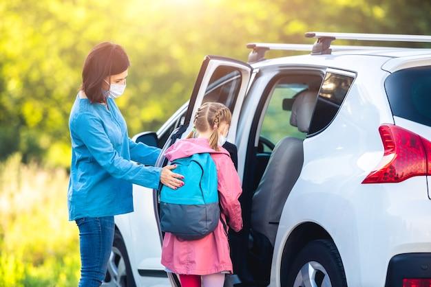 Mutter, die tochter nach dem unterricht während der coronavirus-epidemie ins auto setzt