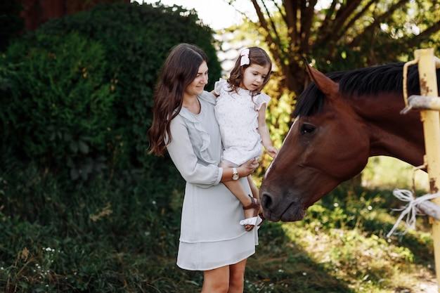 Mutter, die tochter umarmt, genießt, auf bauernhof zu gehen und berührt pferd. junge familie, die zeit zusammen im urlaub, im freien verbringt. muttertag, vatertag, babytag