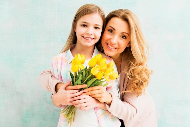 Mutter, die tochter umfasst und tulpen hält