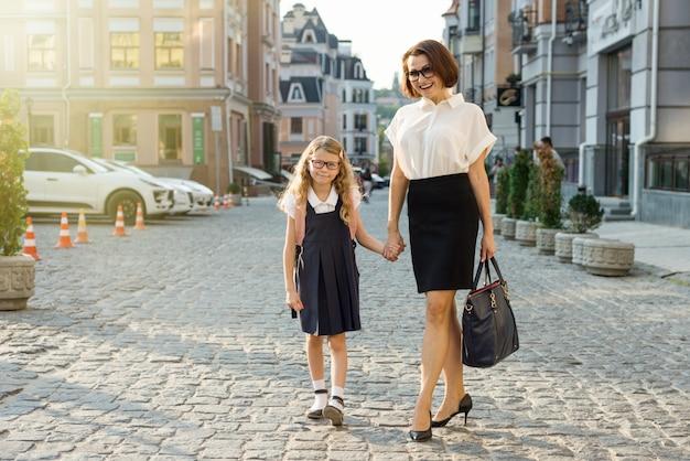 Mutter, die tochter zur schule nimmt und kind an der hand hält