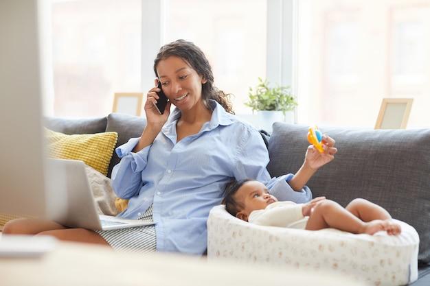 Mutter, die tombola für baby verwendet, während sie mit dem kunden am telefon spricht