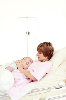Mutter, die um ihrem neugeborenen baby mit copyspace sich kümmert