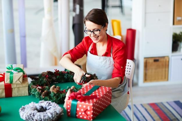 Mutter, die weihnachtsgeschenke einwickelt