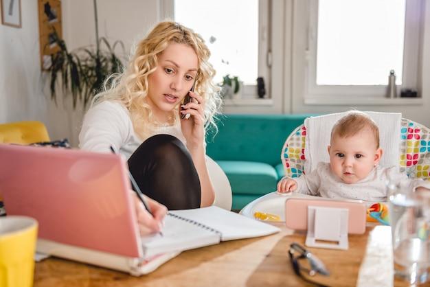 Mutter, die zu hause am intelligenten büro des telefons spricht