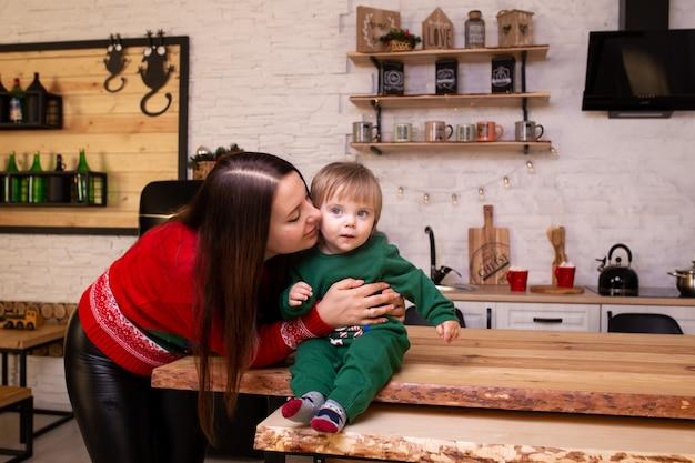 Mutter, die zu hause ihr kind in der küche küsst.
