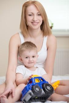 Mutter, die zu hause mit kleinem baby spielt.
