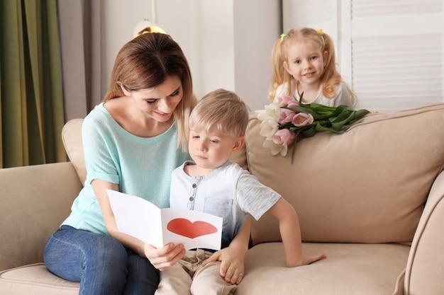 Mutter empfängt grußkarte und blumen von ihren süßen kleinen kindern zu hause children