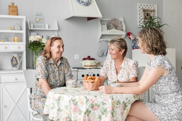Mutter; enkelin und oma sitzen in der küche und lächeln