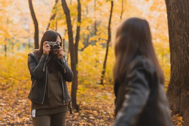 Mutter fotografiert ihre charismatische tochter auf retro-kamera im herbstpark hobbys und freizeit