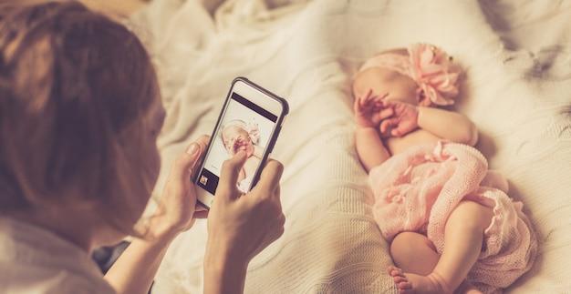 Mutter fotografiert ihre neugeborene tochter, die in eine zarte rosa decke gewickelt ist