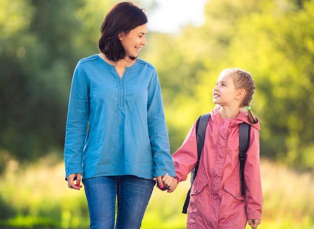 Mutter führt tochter in sonniger natur zurück zur schule