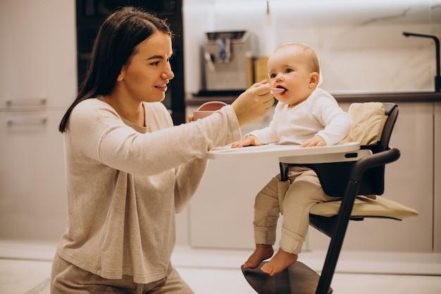 Mutter füttert baby kleinkind, das im stuhl sitzt