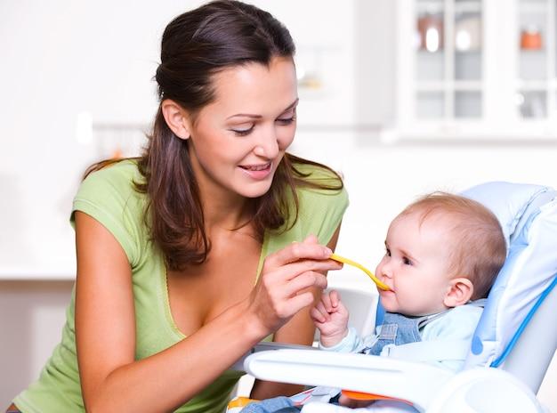 Mutter füttert hungriges baby