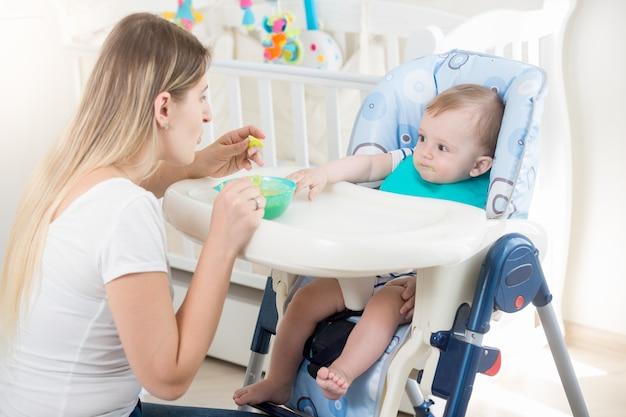 Mutter füttert ihr baby im hochstuhl im wohnzimmer