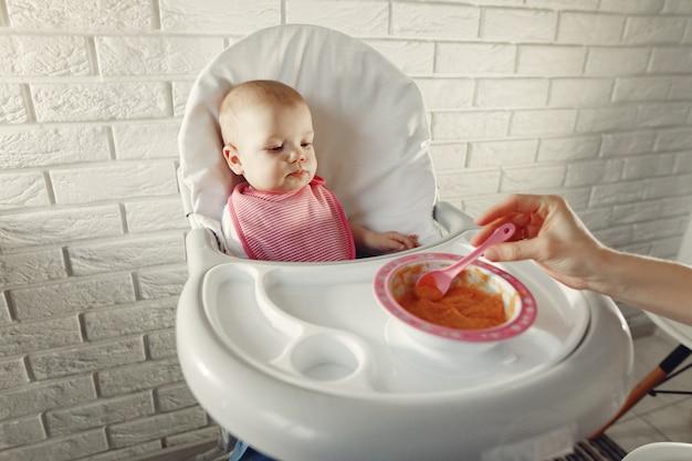 Mutter füttert ihr kleines baby in einer küche